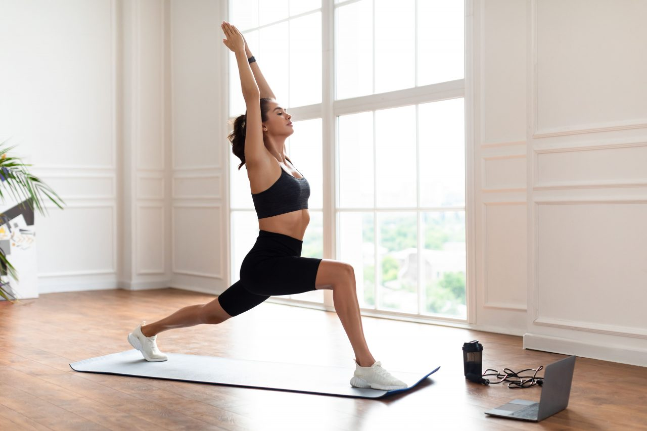 young-woman-doing-forward-lunges-in-front-of-lapto-JJX6AH3-min-1280x853.jpg